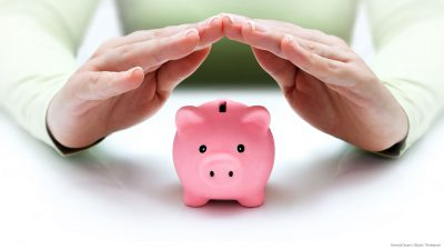 Two hands covering a small pink piggy bank