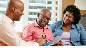 Financial-advisor-talking-to-senior-couple-at-home