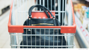 Grocery cart with woman's navy purse inside