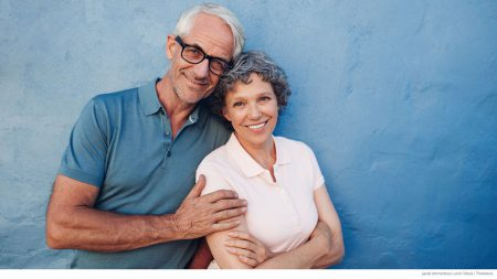 Happy mature couple standing against blue wall