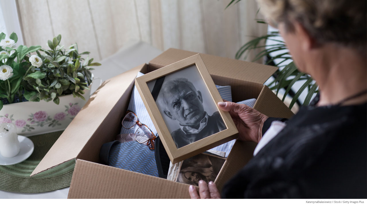 Woman packing a box of deceased husband's possessions; final expense insurance